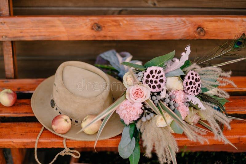 婚姻的花束在长木凳的帽子附近说谎 免版税库存图片