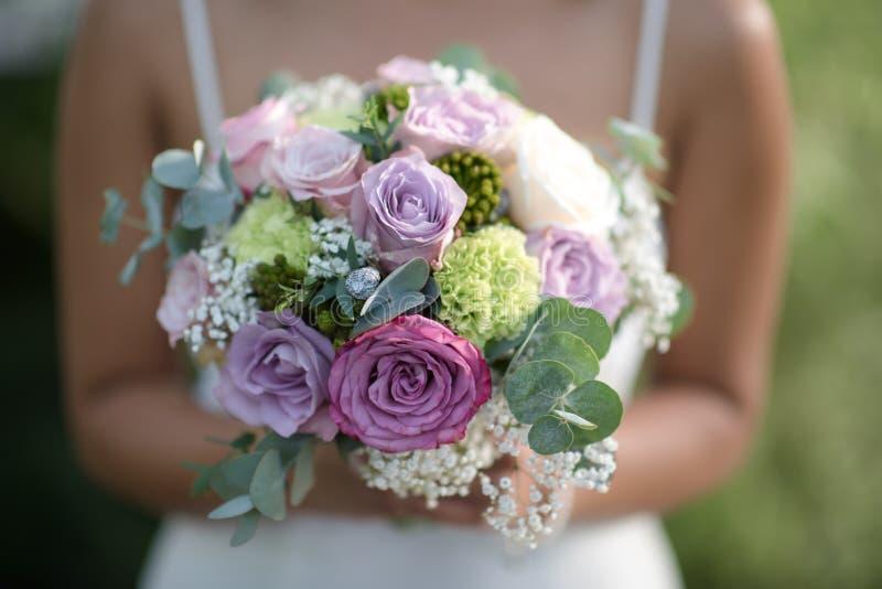 婚姻的花束-美丽的花在一件白色礼服的新娘的手上 免版税库存图片