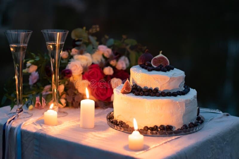 婚姻的装饰 在白色釉的蛋糕与蓝莓和无花果装饰在桌上在晚上与玻璃,被点燃 图库摄影