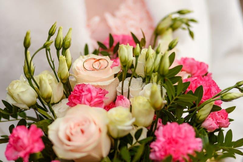 婚姻的金戒指和新娘花束 免版税库存图片