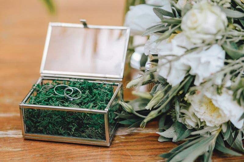 婚姻的金戒指的一个美丽的jewerly玻璃箱子与青苔 在一个新娘的花束附近有白花的在一木backgroun 库存照片