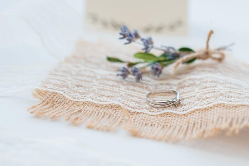 婚姻的钮扣眼上插的花接近的在桌布的照片和圆环 免版税图库摄影