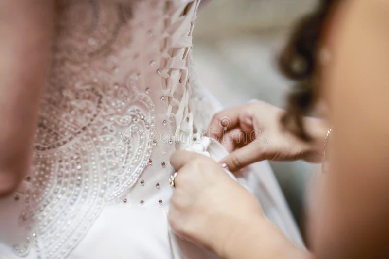 婚姻 女傧相新娘为婚礼之日做准备 女傧相帮助在仪式前紧固一套婚礼礼服新娘 Lu 库存图片