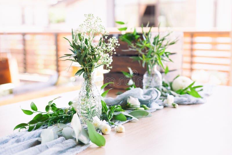 婚姻 洗礼 客人的表,盖用桌布,装饰用蜡烛,透明玻璃花瓶,鲜花 免版税图库摄影