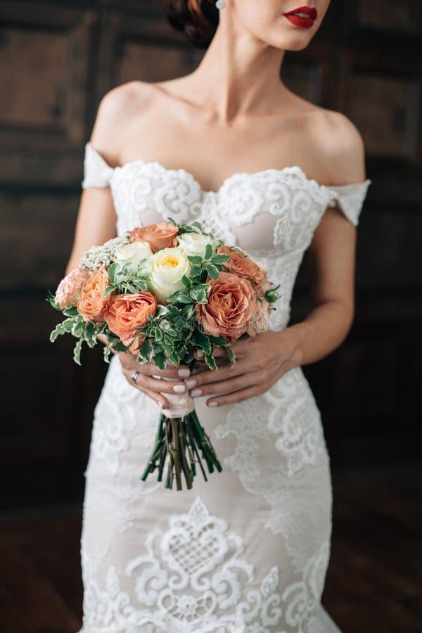 婚姻 花束在新娘手上 wtite礼服的新娘有在黑暗的背景的红色嘴唇的 库存图片
