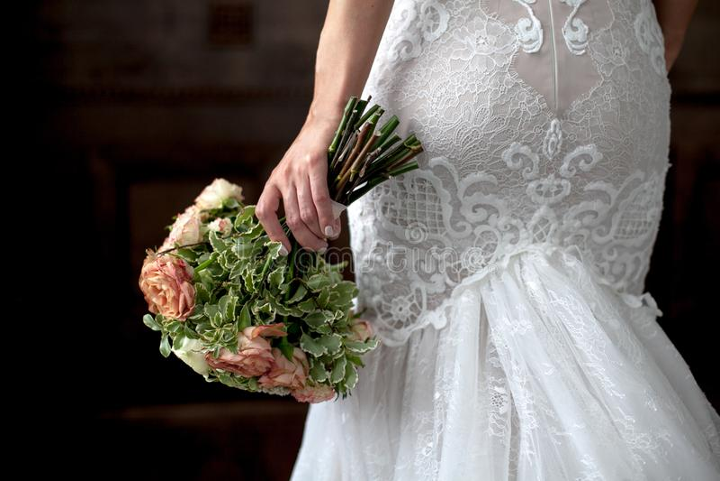 婚姻 花束在新娘手,后面看法上 性感的白色礼服的新娘在黑暗的背景 复制文本的空间 图库摄影