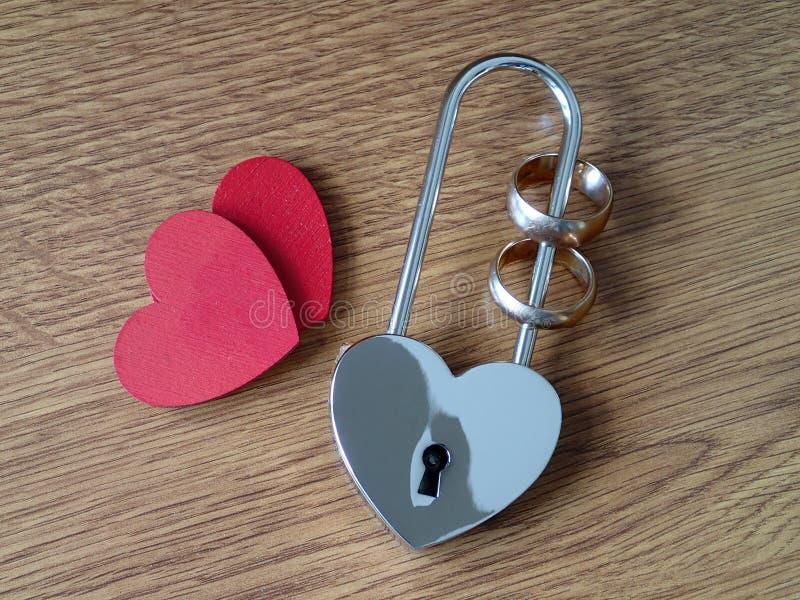婚戒在锁和两红色心脏 免版税库存照片