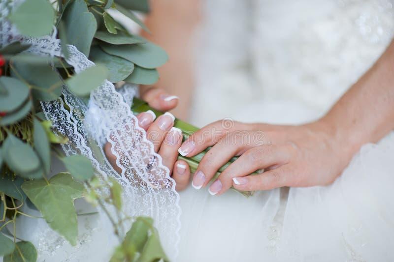 结婚的新娘的手,新娘花束此外 库存照片