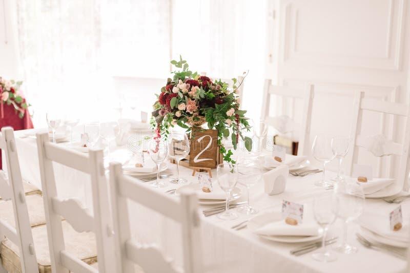 婚礼与红色和桃红色花的桌装饰在白色布料 免版税库存照片