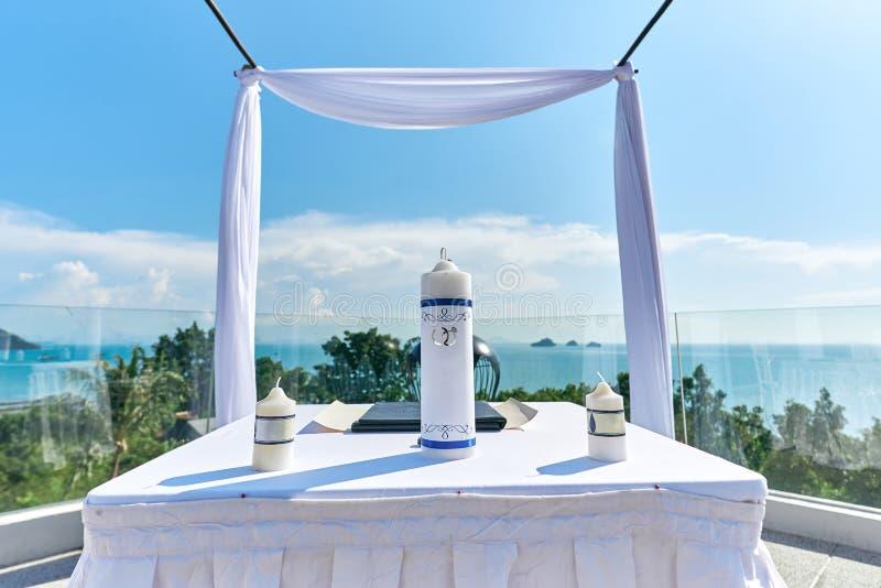 婚礼与蜡烛装饰的法坛设置,在白色桌上的结婚证书 免版税库存图片