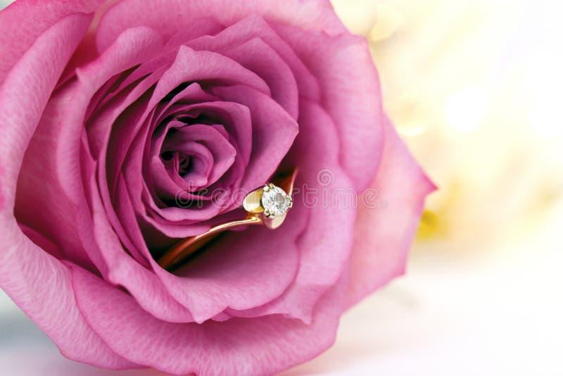 婚礼与金刚石和玫瑰色花的金戒指