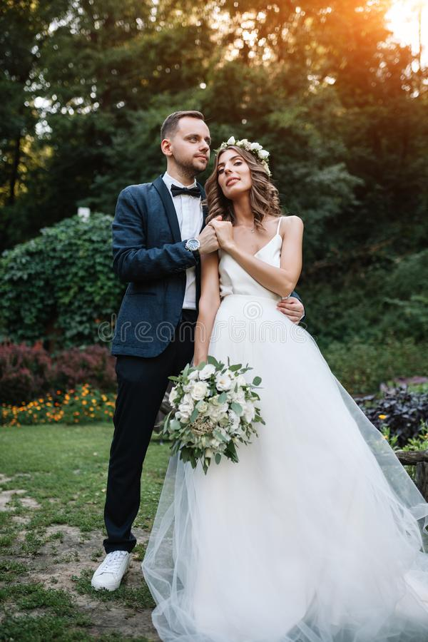 婚礼之日走户外在夏天自然的新娘和新郎 新娘夫妇、愉快的新婚佳偶拥抱以绿色的妇女和人 免版税库存图片