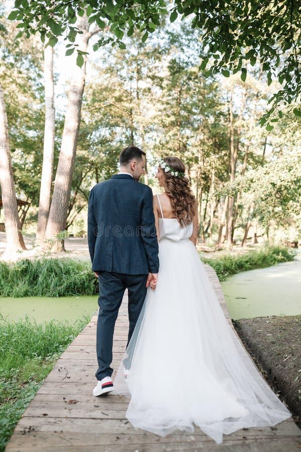 婚礼之日走户外在夏天自然的新娘和新郎 新娘夫妇、愉快的新婚佳偶拥抱以绿色的妇女和人 免版税库存照片