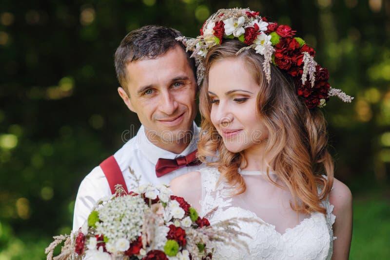 婚礼之日走户外在春天公园的新娘和新郎 免版税库存照片