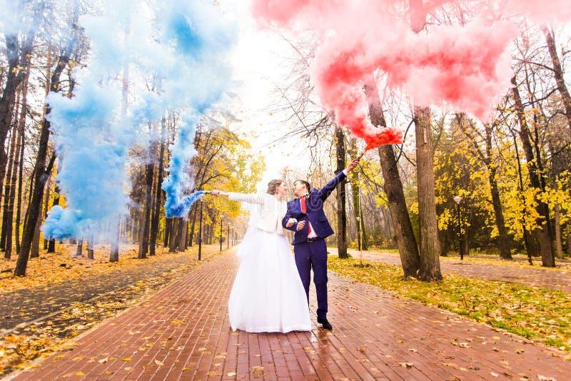 婚礼加上颜色在秋天公园抽烟 颜色炸弹 免版税图库摄影