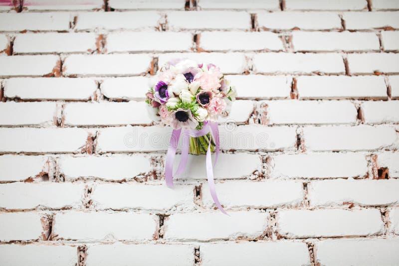婚礼在砖墙背景的牡丹花束 免版税库存图片