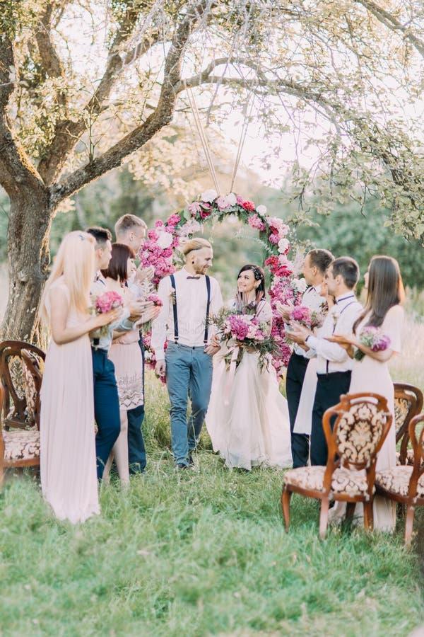婚礼在晴朗的公园 当他们的客人鼓掌时,新婚佳偶走 免版税图库摄影