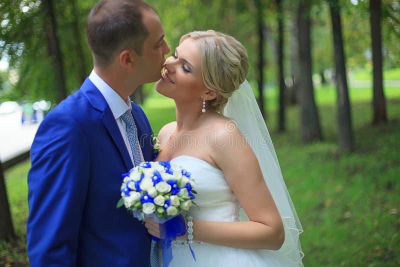 婚礼夫妇新婚佳偶新娘和新郎在爱户外婚礼之日 在新娘天拥抱的愉快的爱恋的夫妇 新婚佳偶机智 库存图片