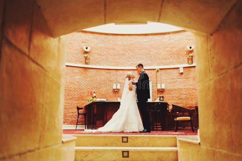 婚礼夫妇看站立在入口的彼此 库存照片