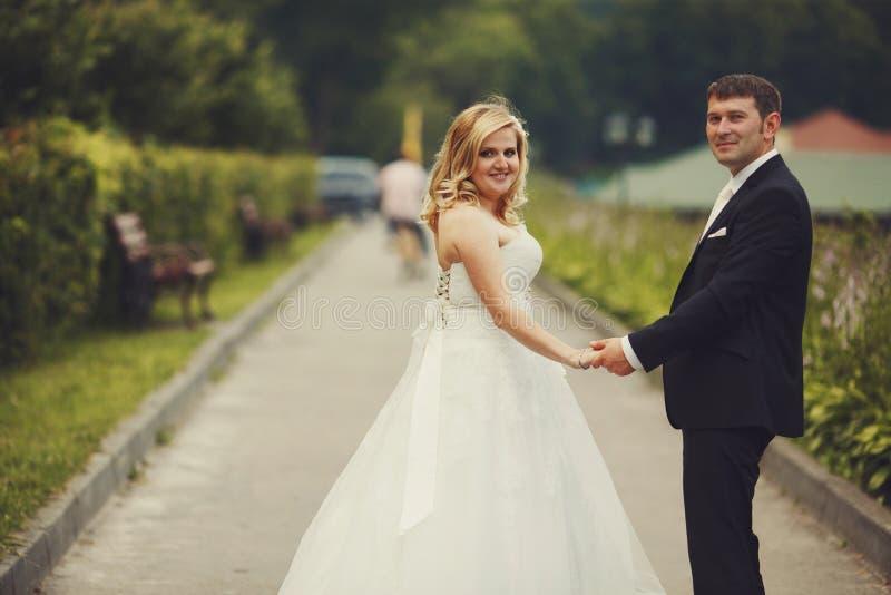 婚礼夫妇结合在一起使他们的手,当走时 库存照片