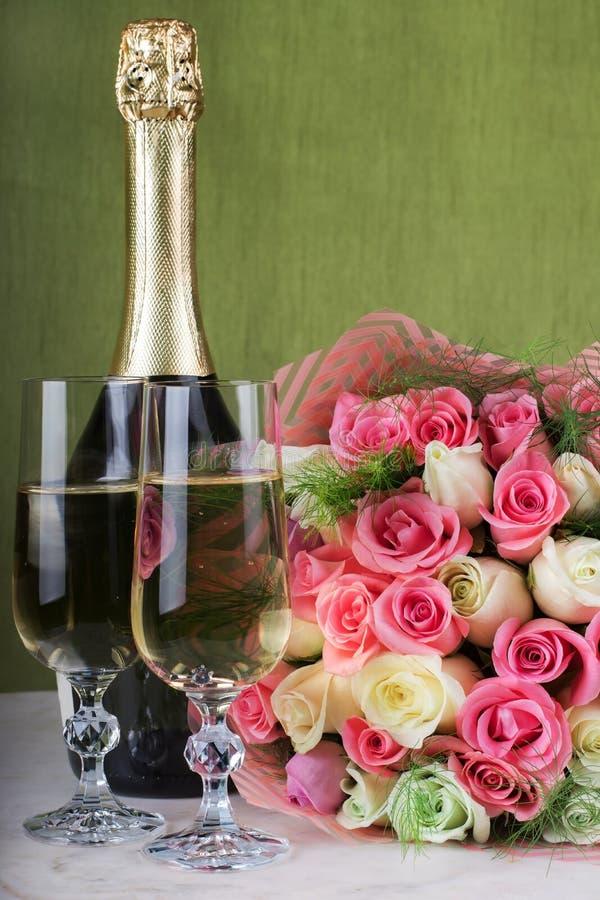 婚礼安排 新娘花束、两杯香槟和一个瓶在一张大理石桌上的香槟 与a的定婚戒指 免版税库存照片