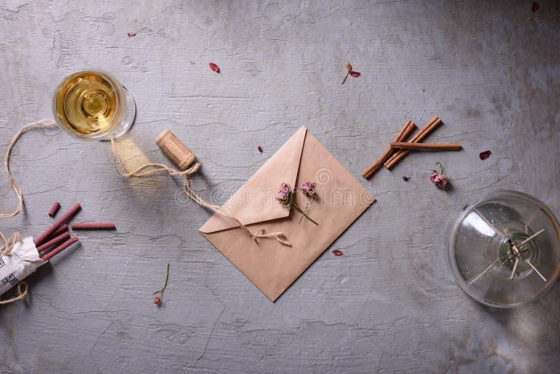婚礼或情人节 杯酒、信封和芳香在灰色背景黏附 情书或浪漫消息 上面竞争 免版税库存图片