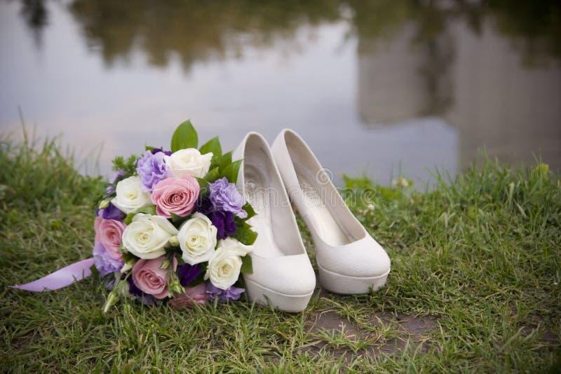 婚礼摄影 鞋子和新娘的花束 库存照片