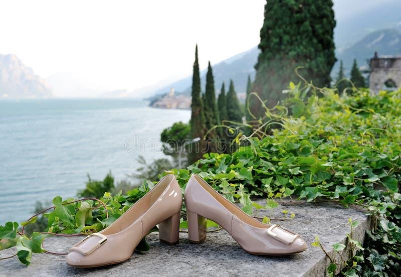 婚礼新娘鞋子,在背景Garda湖 库存图片