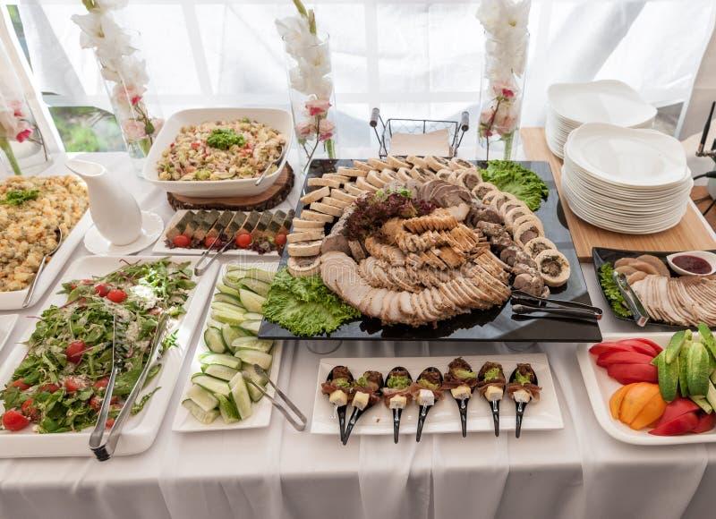 婚礼桌用食物 快餐和开胃菜在表上 鱼和生肉与菜 切的烟肉肉 免版税库存照片