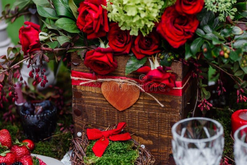 婚礼桌装饰:开花与玫瑰、站立在木箱的莓果、草本和绿叶的构成 新娘细节和decorat 免版税库存照片