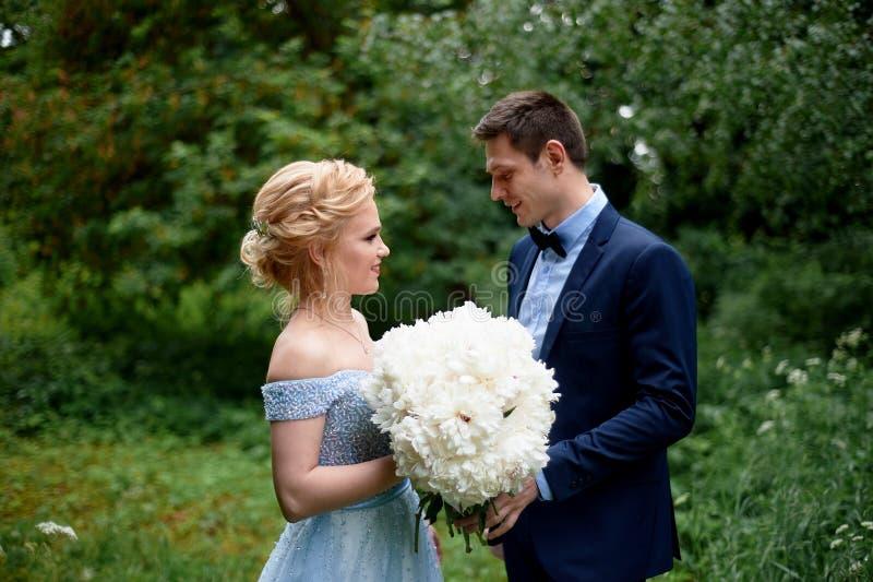 婚礼照片写真和步行 新郎和新娘、新娘` s蓝色礼服和牡丹花束  在公园,  免版税库存图片