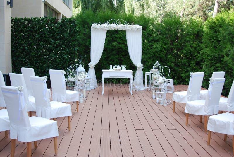 婚礼的区域,装饰用白花 美丽的曲拱,用花装饰的白色椅子 库存照片