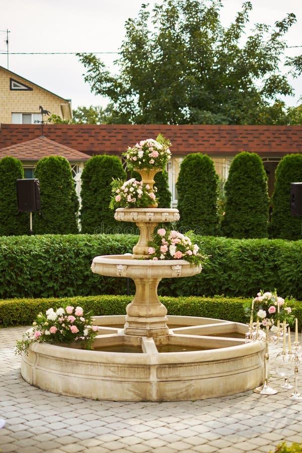 婚礼的装饰-在喷泉的花 背景钮扣眼上插的花看板卡装饰装饰邀请婚姻白色的珍珠玫瑰 库存图片