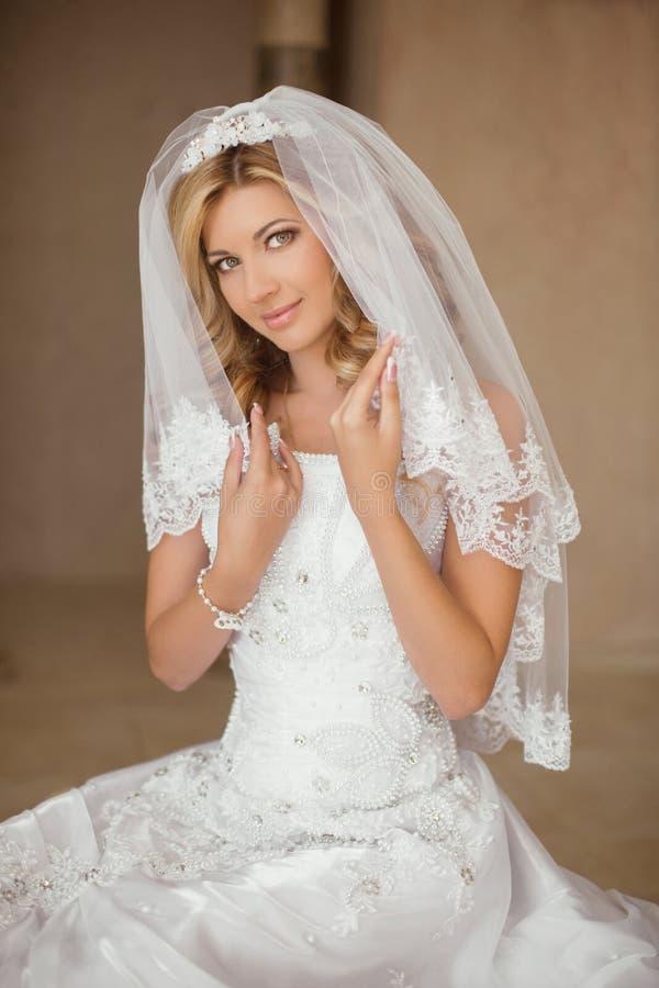 婚礼礼服和新娘面纱的p美丽的微笑的新娘妇女 免版税库存照片