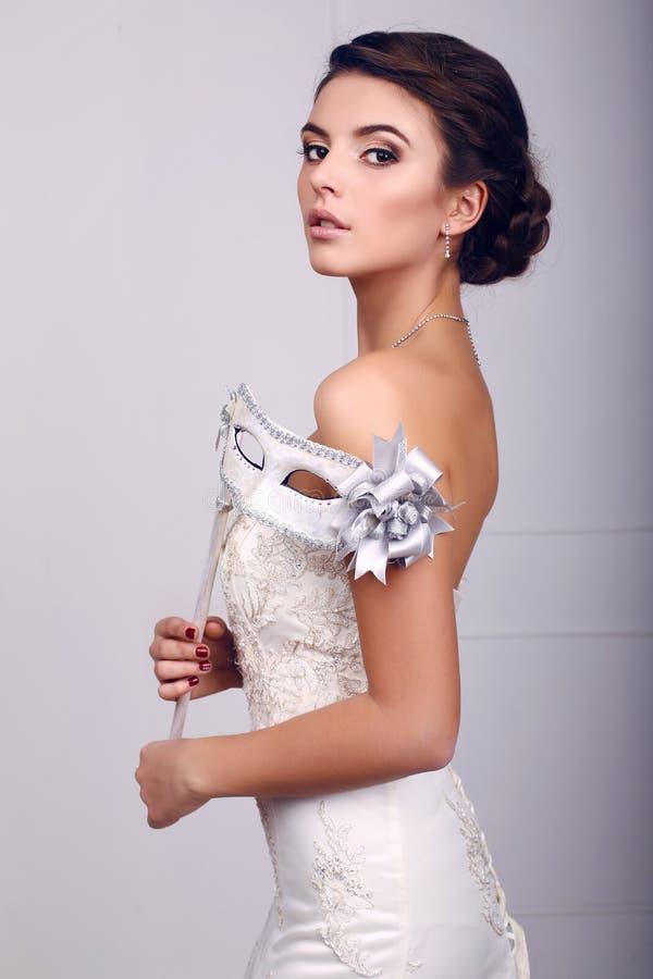 婚礼礼服的典雅的新娘与面具在她的手上 库存照片