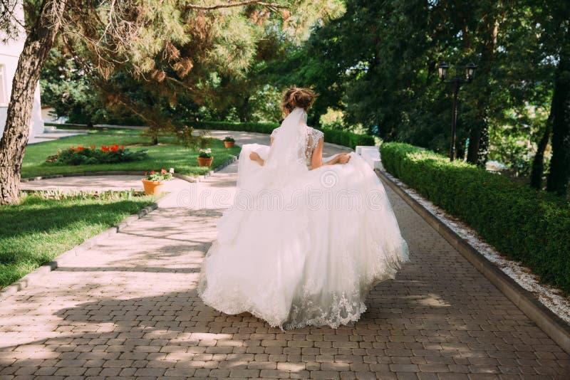 婚礼礼服的女孩在她的手上采取了裙子并且跑了到心爱会议的 新娘跑掉 库存图片
