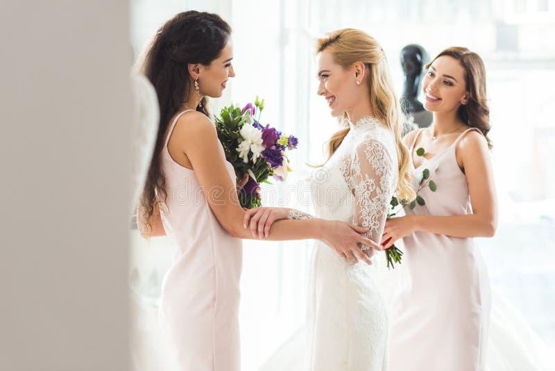 婚礼礼服的愉快的妇女与花 库存照片