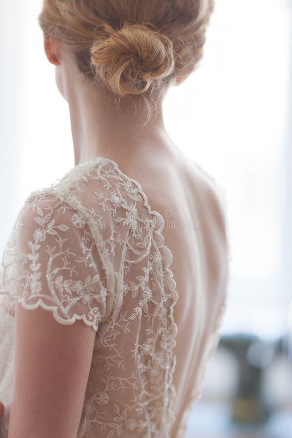 婚礼礼服的新娘与从后面的鞋带 库存照片