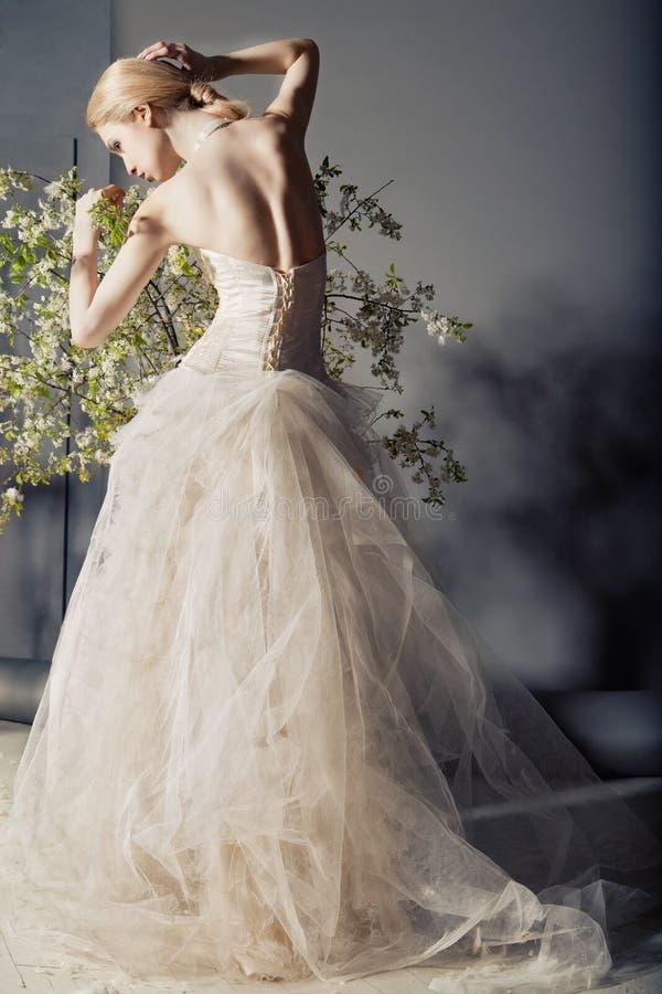 婚礼礼服的新娘在与花的灌木之后 免版税库存图片