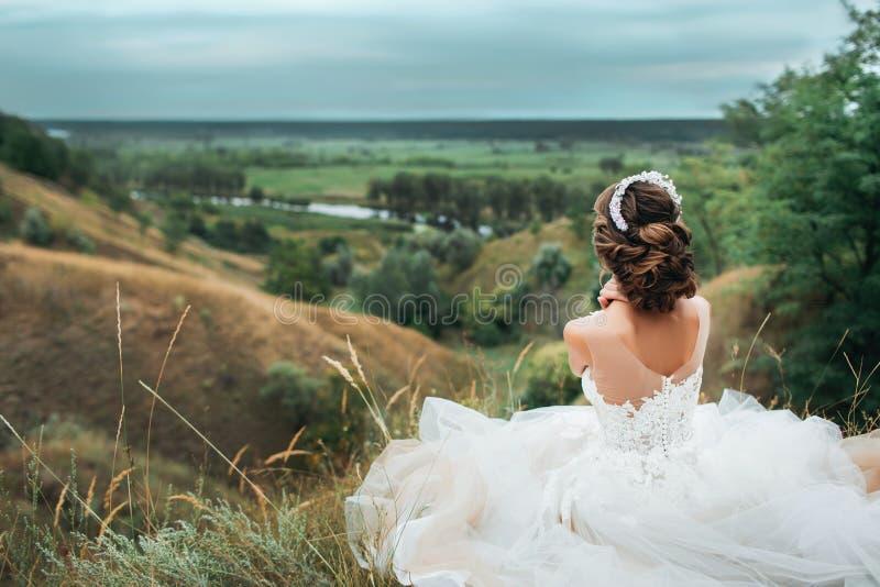 婚礼礼服的新娘坐小山 免版税库存图片