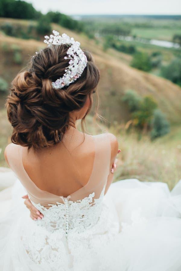婚礼礼服的新娘坐小山 免版税库存照片