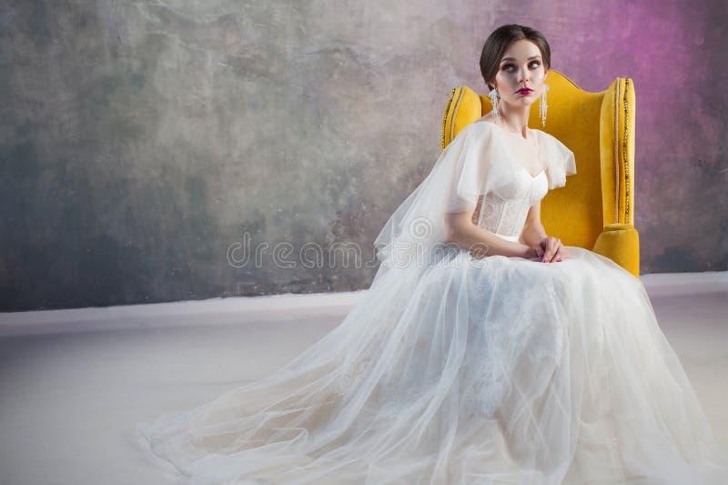 婚礼礼服的美丽和时髦的新娘在灰色织地不很细背景的演播室 免版税库存照片