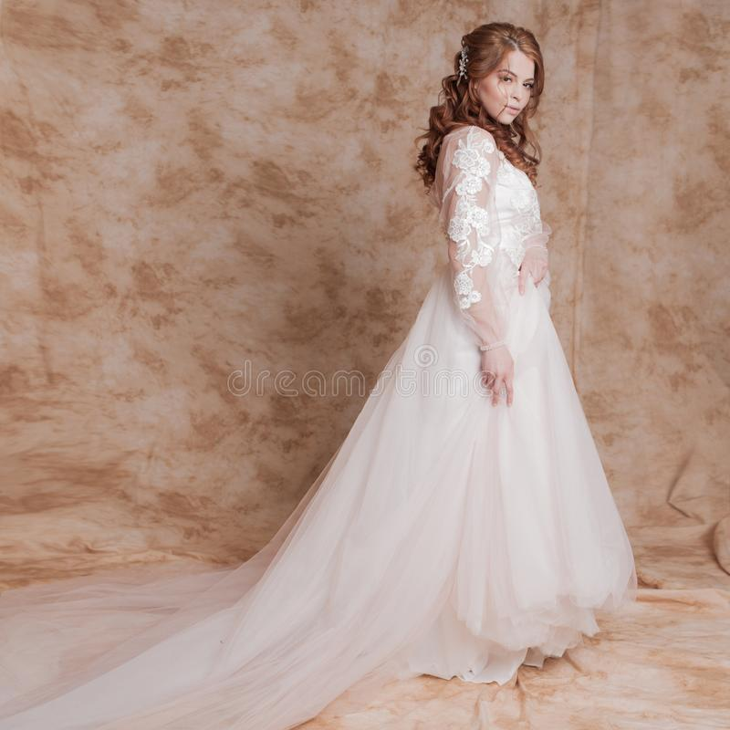 婚礼礼服的美丽和浪漫新娘与长的袖子 婚礼礼服的年轻红发妇女 免版税库存照片