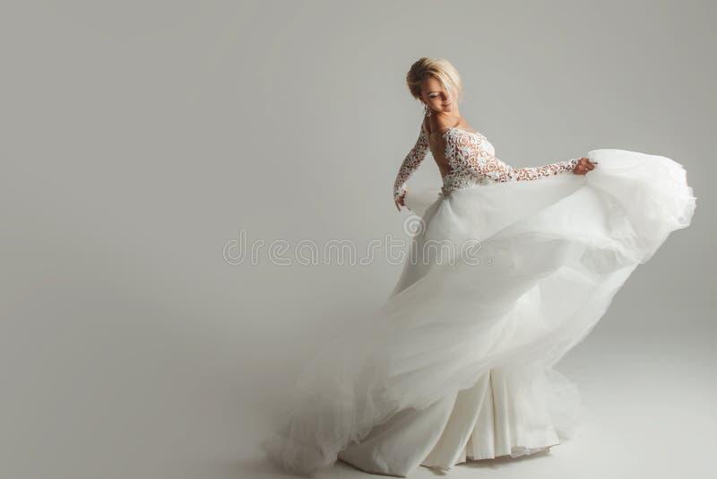 婚礼礼服的美丽的可爱的新娘与长的宽下摆女裙、白色背景、舞蹈和微笑 免版税库存图片