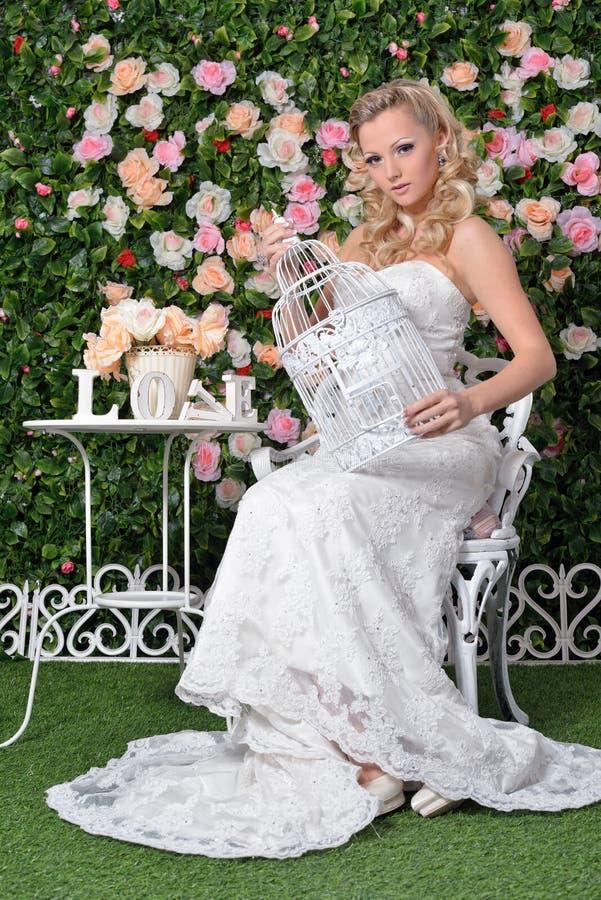 婚礼礼服的美丽的妇女在有花的庭院里。 免版税库存图片