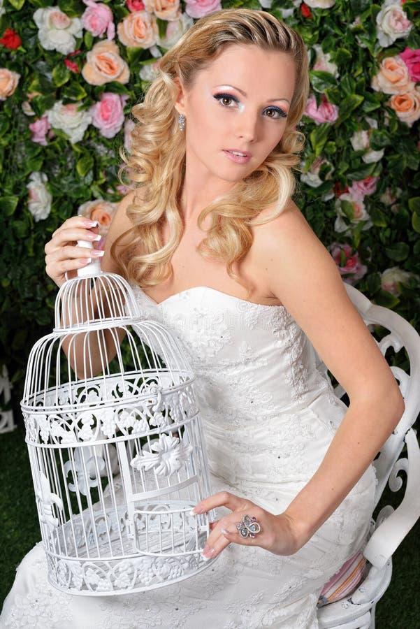 婚礼礼服的美丽的妇女在有花的庭院里。 库存图片