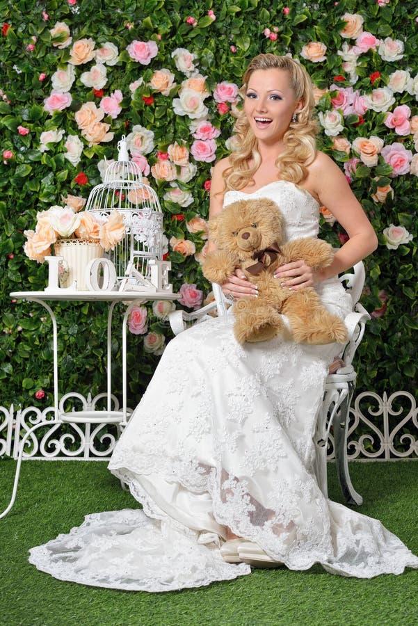 婚礼礼服的美丽的妇女在有花的庭院里。 免版税库存照片