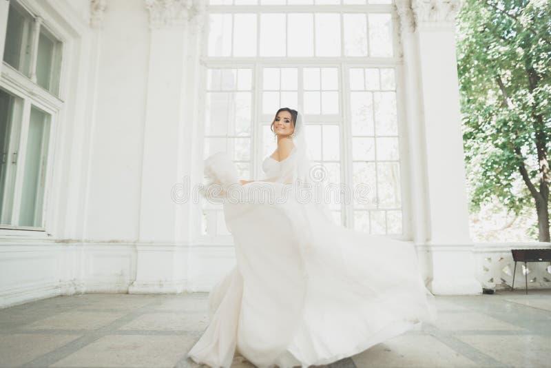 婚礼礼服的美丽的新娘与长的宽下摆女裙、白色背景、舞蹈和微笑 库存图片