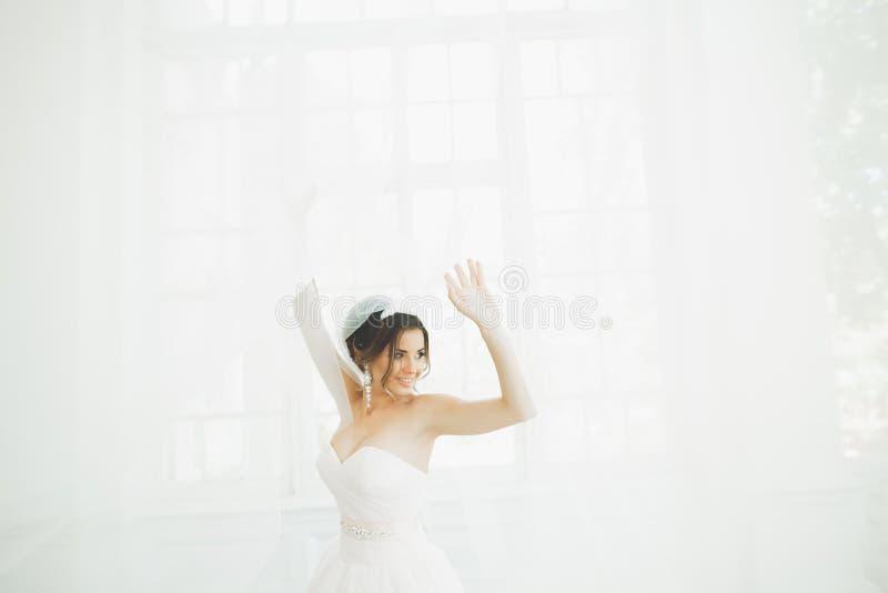 婚礼礼服的美丽的新娘与长的宽下摆女裙、白色背景、舞蹈和微笑 免版税库存图片
