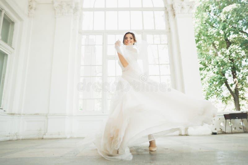 婚礼礼服的美丽的新娘与长的宽下摆女裙、白色背景、舞蹈和微笑 免版税库存照片